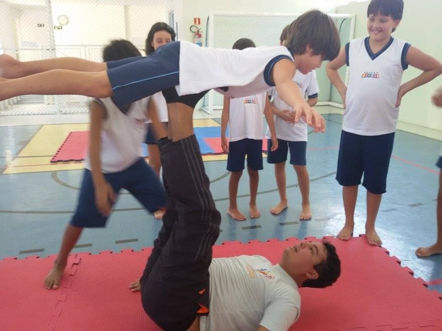 O educador demonstra para alunos do 5º ano o movimento ginástico classificado: posição do avião